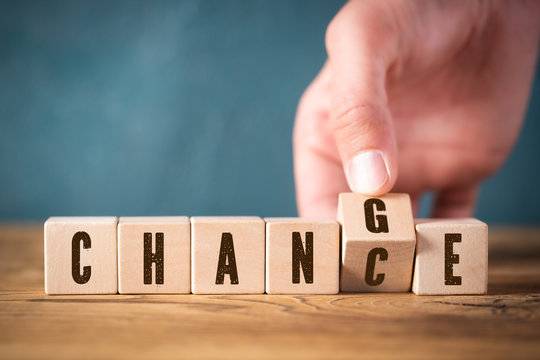 "Hand flips one of six cubes with letters, turning the word ""change"" to ""chance"""