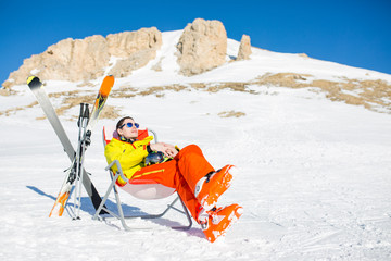 Image of sports man sitting on chair next to skis and sticks on background of snowy mountains