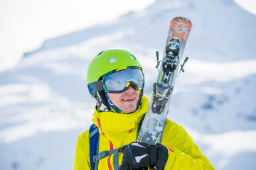Photo of sporty man wearing helmet with ski on his shoulder