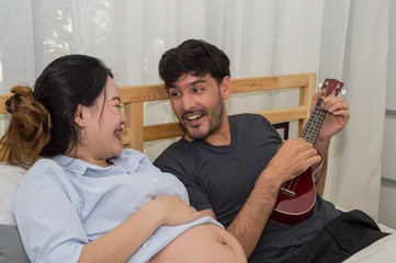 Men playing music for pregnant women in the bedroom.