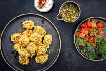 Traditionelle kasachische gedämpfte Manti mit Hackfleisch und Tomaten Salat  als Draufsicht auf einem Modern Style Teller