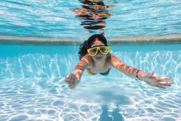 Girl in mask dive in swimming pool
