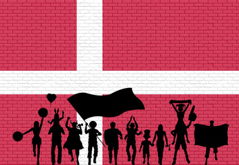 Danish supporter silhouette in front of brick wall with Denmark flag