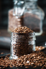 Flax seeds in glass jar, brown background, selective focus