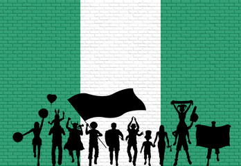 Nigerian supporter silhouette in front of brick wall with Nigeria flag