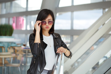 Lovely Asian girl in stylish casual clothes in a cafe.