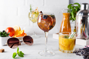 A glass of cocktail with cinnamon, berries and brown sugar and a glass with an orange cocktail or fresh and tonic