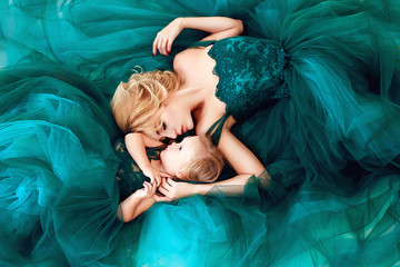 Portrait of a beautiful young mother with a cute blonde daughter dressed in elegant green dresses.