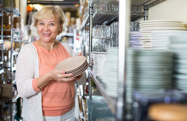 female buyer with clay plates in the tableware store