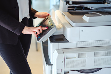Woman pressing button on a copy machine in the office