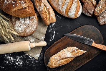 Fresh bread, wooden board and cutting knife on black table