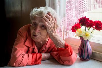 Elderly woman looks sadly sitting near the window.