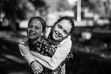 Two sisters girls teenagers having fun looking at the camera. Black and white photo.