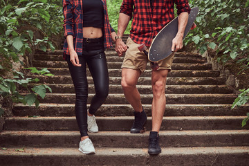 Young hipster couple, walk in a park, holding hands, descending the stairs.