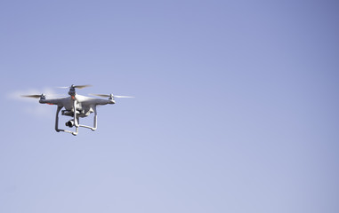 Flying Quadcopter Drone in the blue sky background. Free copy text space.