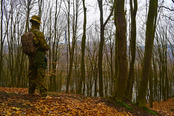 Rear view of the military man with a backpack in the forest above the height.