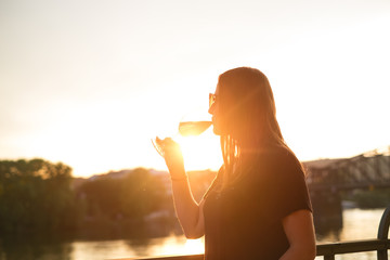 Woman drinking a wine in the city during a sunset. Glass of red wine. Concept of free time in the city and drinking alcohol.