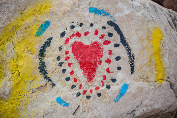 A red heart drawn on a rock symbol of a strong feeling. A solid and lasting love painted in color on a stone by the sea. Colorful graphic elements made by hand on the stones.