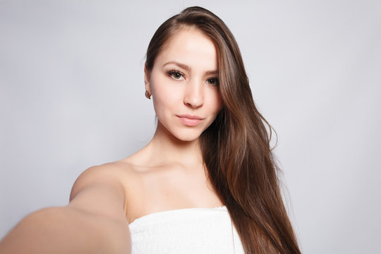 beauty, skin care and people concept - Spa Woman. Beautiful Girl After Bath Touching Her Face. Perfect Skin. Skincare. Selfie time. Young happy woman taking selfie. Pampering. Treatment
