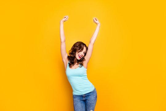 Portrait of positive slim girl holding raised hands modern hairdo enjoying sun light isolated on yellow background