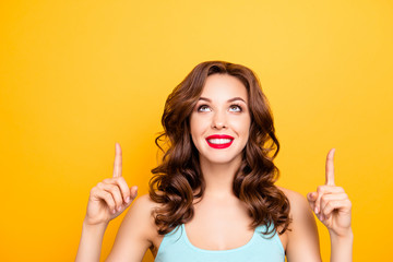 Portrait of pretty trendy girl with modern hairdo pointing two forefingers up showing copy space empty place isolated on yellow background, advertisement concept Wall mural