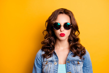 Portrait of trendy cool girl in summer glasses sending kiss with pout lips having fashionable look modern hairdo isolated on yellow background. Rest relax leisure fun concept