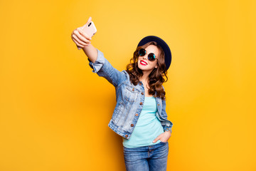 Portrait of charming pretty blogger cool coquette holding hand in pocket of pants shooting selfie on front camera of smart cell phone having video-call isolated on yellow background
