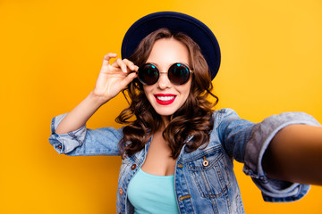 Portrait of trendy pretty tourist with beaming smile shooting self portrait on front camera holding eyelet of glasses on face wearing jeans jacket isolated on yellow background, travel tourism concept
