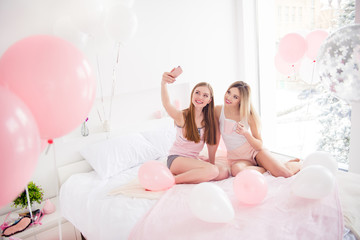 Portrait of stylish slim attractive charming pretty blonde girls in night wear, shorts having meeting indoor, having cup of tea, shooting selfie on front camera, using smart phone on sleepover party