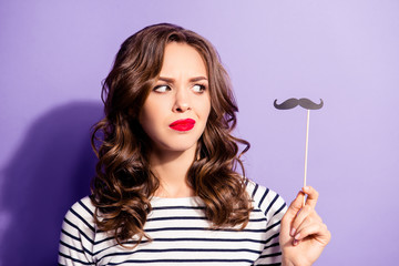 Portrait of unhappy confused girl with red lipstick looking at black carton cutout paper mustache on stick in hand isolated on violet background