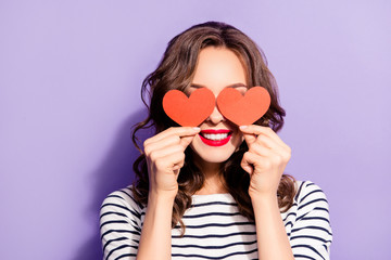 Portrait of lovely creative girl with white teeth red pomade covering closing eyes with two carton paper small little heart figures love signs isolated on violet background