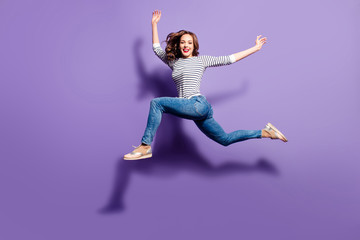 Portrait of crazy foolish girl jumping over in the air looking at camera having good stretching isolated on violet background, people life energy lifestyle concept