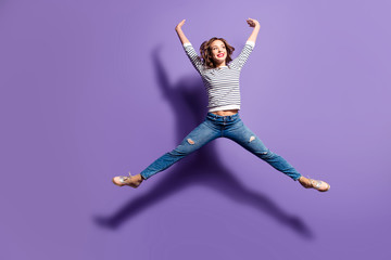 Portrait of funny comic girl jumping in the air making star figure looking away isolated on violet background full of energy powerful people concept