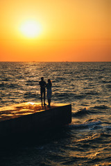 Silhouette of couple standing at the pier, watching the sunrise at the beach summer time