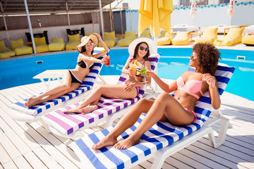Side profile half-tirned photo of three trio charming excited careless romantic lovely gentle cute beautiful attractive women lying on striped sunbeds toasting cheers with beverages in hands