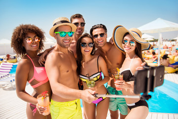 Diversity sunbathing sunshine tanned happiness eyewear spectacles cell cellphone modern technology video call concept. Group of excited funky fashionable amusing joyful teens taking selfie