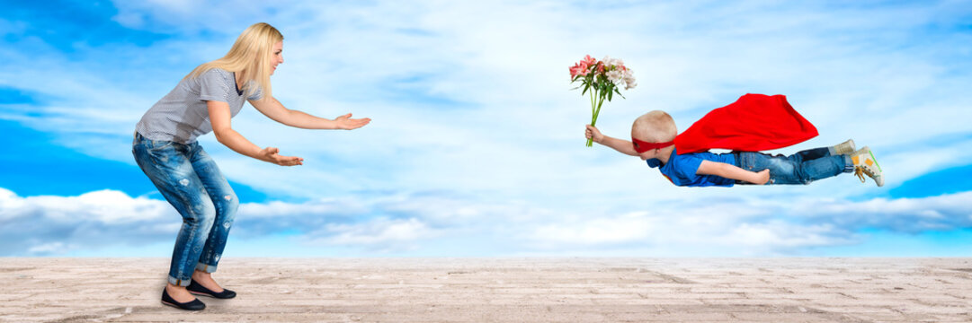 The son in the costume of a superhero flies with a bouquet of flowers to her beloved mother.