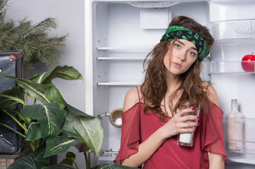 Tired girl with glass of milk at fridge in kitchen. Sensual woman at open refrigerator. Beauty woman with hippie hair and look. Beauty and look. What do I want? Food concept. diet and health
