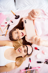 Portrait of joyful, cheerful, laughing, pretty, charming, stylish, successful girls in pink, white outfit having smart phone in hands shooting selfie lying on bed with variety of makeup, cosmetics