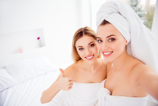 Cheerful, charming, pretty couple, stylish, sexy models sitting on bed after bath, procedures, wrapped in towels showing thumb up with finger, shooting self portrait on front camera, enjoying meeting