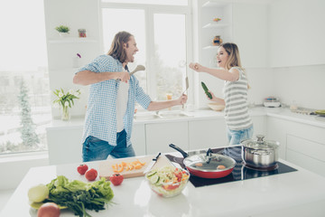 Portrait of cheerful positive partners using kitchenware and vegetables fighting in modern white kitchen near table stove having vacation spending time indoor together