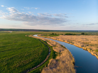 Small river meanders in the midst of green fields and meadows at sunset. Beautiful landscape with a bird's eye view on a summer evening