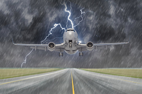 Lightning strike bolt during a thunderstorm and heavy rain in the aircraft airport during landing.