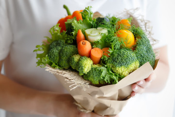 Bouquet of broccoli, celery, carrots, paprika and lettuce in the hands of a woman