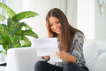 Close-up of an office worker. Woman, enjoying the good news in writing. An euphoric girl is happy after reading good news in a written letter, approving a loan, raising her job.
