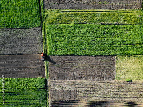 Wall mural Aerial view of tractor pulling drill sowing seed In field