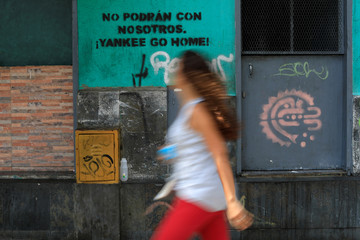 """A woman walks past a graffiti that reads: """"You will not be able to do it with us. Yankee go home"""" in downtown Caracas"""