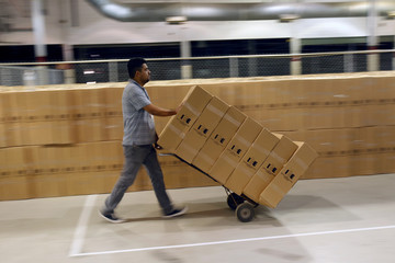 An employee of the Chihuahua state Electoral Institute moves boxes with voting materials to be distributed throughout the state, at a warehouse in Ciudad Juarez