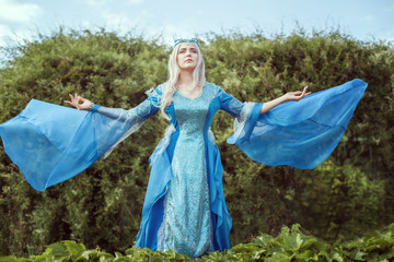 Young woman elf stands in the forest and looking up. She spread her hands, her dress develops in the wind.