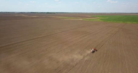 Wall Mural - Tractor cultivates the field, spring works on farmlands. Photo from the drone